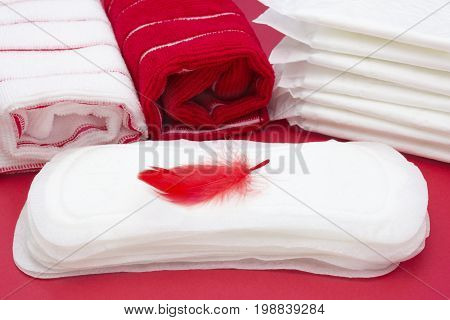 Terry bath towels red feather on menstrual woman pad for blood period hygiene. Woman critical days gynecological menstruation cycle. Medical concept photo. Menstruation sanitary hygiene protection