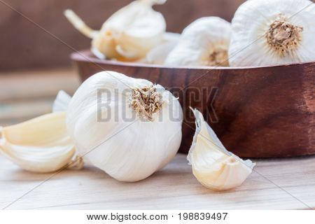 Garlic Cloves and Garlic Bulb in vintage wooden bowl. Garlic is a Thai herb and is a spice. Usually put in many kinds of food.