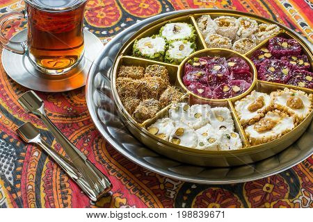 Eastern sweets. Assorted traditional Turkish delight (Rahat lokum) on background with national ornaments. Turkish delight with different nuts coconut shavings and powdered sugar