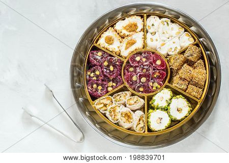 Eastern sweets. Assorted traditional Turkish delight (Rahat lokum) on gray stone background. Turkish delight with different nuts coconut shavings powdered sugar and tongs for sweets. Top view