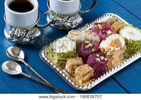 Eastern sweets. Assorted traditional Turkish delight (Rahat lokum) on blue wooden background. Turkish delight with different nuts and coconut shavings coffee in cups and spoons