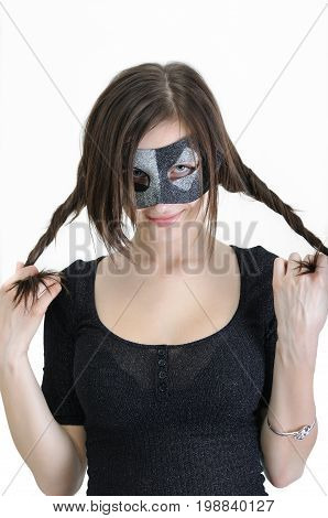 portrait of young stylish woman in carnival mask looking at camera on white background