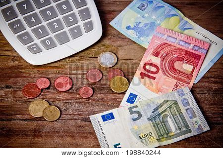 european money and calculator on wooden table