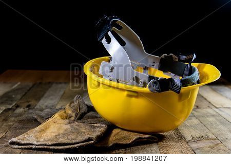 Yellow Helmet And Welding Gloves. Old Wooden Table.