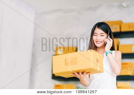 Small business owner Asian woman hold package box using mobile phone call receiving purchase order working at home office. Online marketing delivery startup SME entrepreneur or freelance concept. With copy space