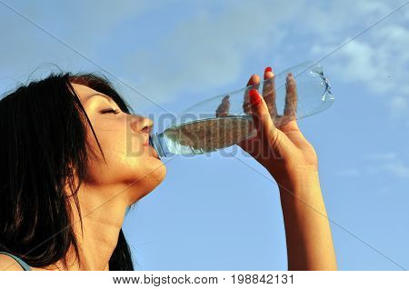 Thirst.Thirsty girl drinks cold water in hot day