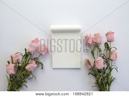 Notepad with roses on white background. Romantic flat lay banner template with text place. Wedding card backdrop with roses and blank white page notepad. Gentle pink flowers on white table top view