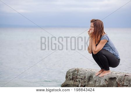Woman sitting alone and depressed at seaside