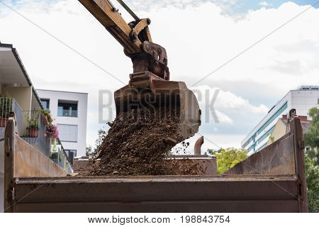 Bucket excavator loads building rubble on a construction site on truck