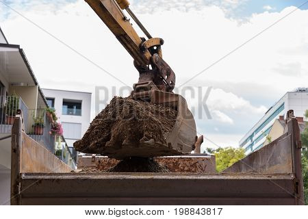 Bucket excavator at excavation site on a construction site loading rubble on truck