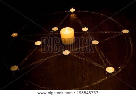 Halloween Mystic pentagram with fired candles in darkness on wooden background