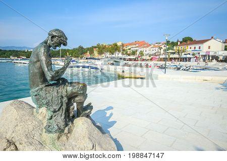 NJIVICE CROATIA - JUNE 24 2017 : Sculpture of a fisherman repairing the net at the waterfront in Njivice island of Krk Croatia.