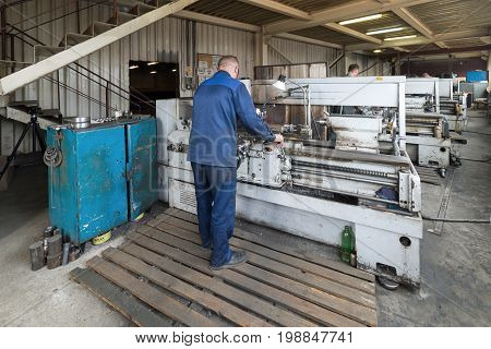 LIPETSK, RUSSIA - JUNE 15, 2017: Lipetsk Machine Tool Plant, turner works behind a lathe