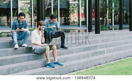 Multi-ethnic group of young college students or freelance coworker using smartphone and laptop computer together. Lifestyle with infomation technology gadget education or social network concept