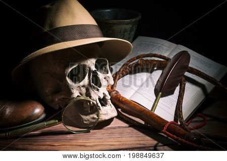 Adventure and archeology concept. Skull with fedora hat, bullwhip, book, quill, shoe, mortyr and magnifying glass on wooden table and black background. Still life