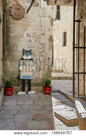 Kotor Montenegro - June 8 2017: A typical view in one of the narrow streets in a very tourists friendly old town of Kotor with a shop sign of a cat.
