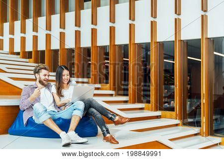 Multi-ethnic college student couple celebrate together with laptop on stairs in university campus or modern office. Information technology education or startup business concept. With copy space