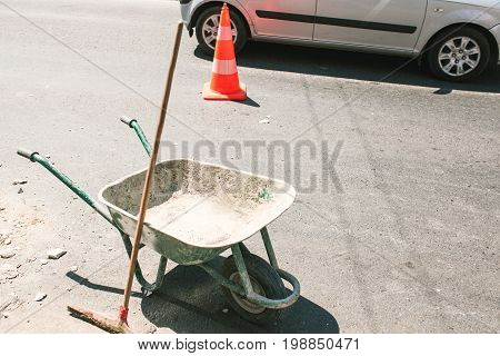 Image of rustic dirty construction wheelbarrow with push broom on the street, orange road construction cone in the background.