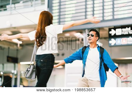 Asian girl picking up her boyfriend at airport's arrival gate welcomes back home from studying or working abroad. Young couple love and hug honeymoon or traveling concept
