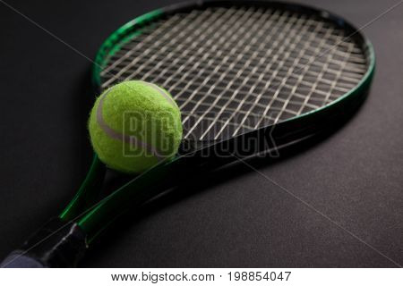 Close up of fluorescent yellow tennis racket and ball on black background