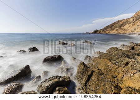 Rocky Rancho Palos Verdes coast with motion blur waves in Los Angeles County, California.