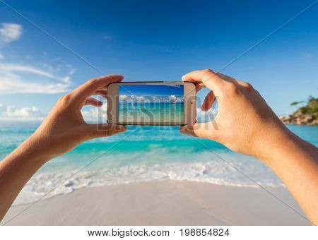 Female hands taking a picture of the beach with a cellphone