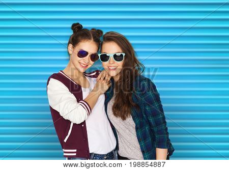 people, summer and fashion concept - happy smiling pretty teenage girls or friends in sunglasses over blue ribbed background