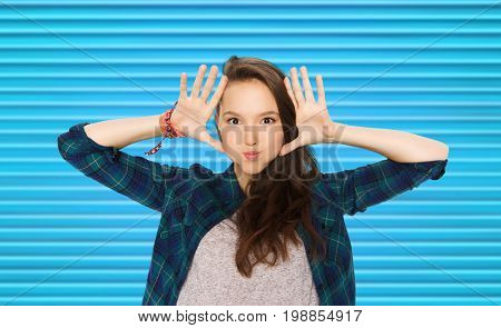 people and teens concept - happy smiling pretty teenage girl making faces and having fun over blue ribbed background