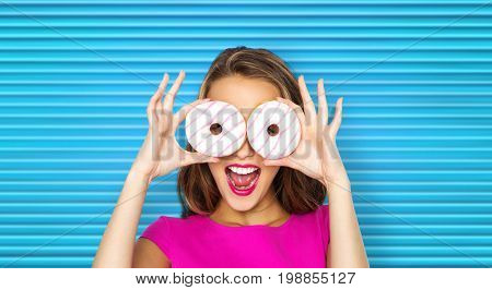 people, sweets and fast food concept - happy young woman or teen girl in pink dress having fun and looking through donuts over blue ribbed background