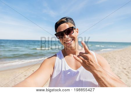 summer holidays, gesture and people concept - happy smiling young man in sunglasses and hat taking selfie and showing rock sign on beach