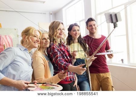 creativity, education, technology and people concept - group of artists or students with brushes and palettes taking selfie by smartphone and monopod at art school studio