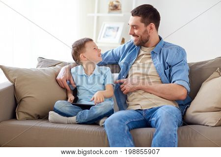 family, fatherhood and people concept - happy father and little son with tablet pc computer sitting on sofa at home