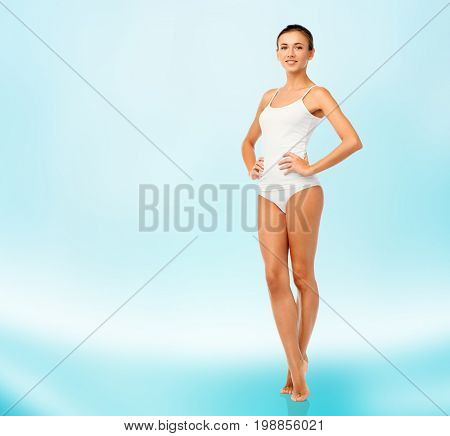 beauty, people and bodycare concept - beautiful young woman in white underwear over blue background