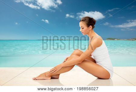 beauty, depilation, epilation, people and bodycare concept - beautiful woman touching her smooth bare legs over exotic tropical beach background