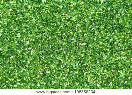 Green abstract background. Green glitter closeup photo. Green shimmer wrapping paper. Sparkling glitter festive backgrop. Christmas greeting card template. Glitter macrophoto. Shiny green texture