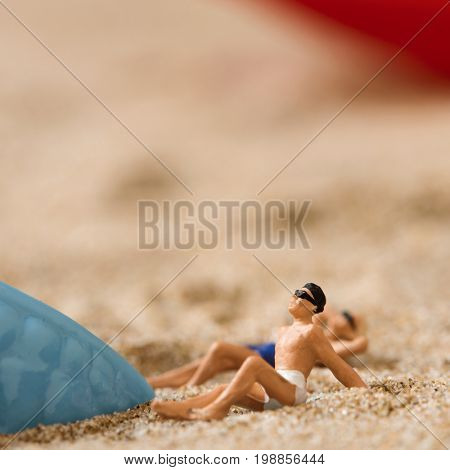 miniature man and miniature woman wearing swimsuit relaxing next to a blue plastic starfish on the sand of the beach
