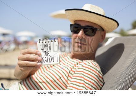 closeup of a young caucasian man relaxing in a sunlounger in the beach showing a spiral notepad with the text closed for vacation handwritten in the first page