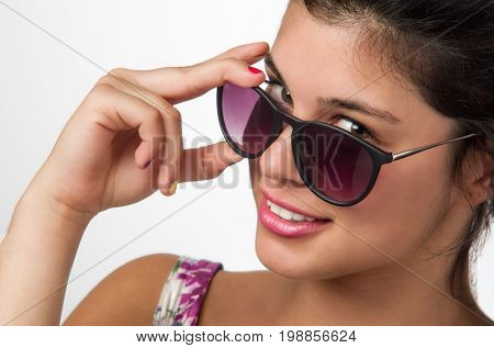 Portrait of a pretty brunette teenager wearing sunglasses and pink lipstick