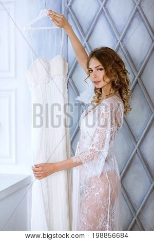 Female portrait of cute lady in white robe indoors. Close up beautiful sexy model girl in elegant pose with wedding dress. Closeup beauty woman with hairstyle and makeup. Glamorous brunette bride