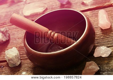 Tibetan singing bowl with stick with crystals on wooden board