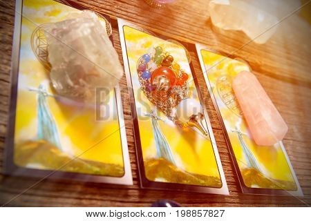 Tarot cards, dowsing tool and crystals on a wooden board