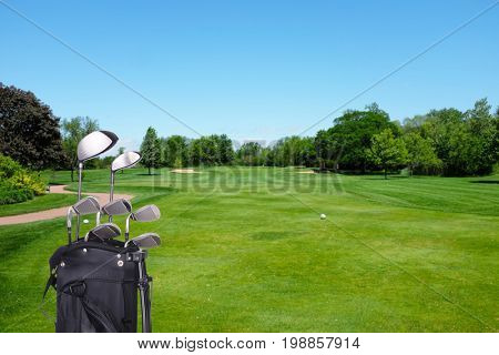 Closeup of a golf bag and clubs on the tee-box of a golf course.