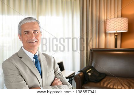 Businessman in hotel room with arms folded and looking at camera.