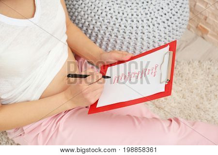 Pregnant woman studying list of names at home. Concept of choosing baby name