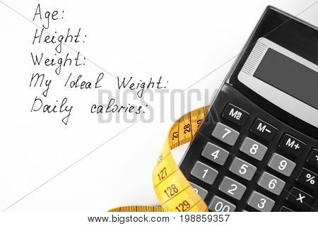 Diet concept. Measuring tape and calculator on sheet of paper