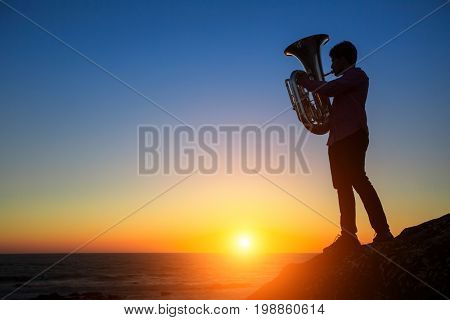 Silhouette of musician play Tuba on sea beach at magical sunset.