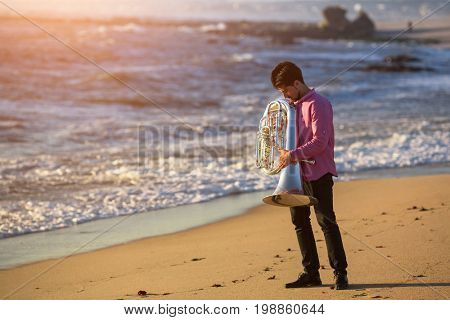 Musician with Tuba on the sea coast during surf. Romantic Instrument.