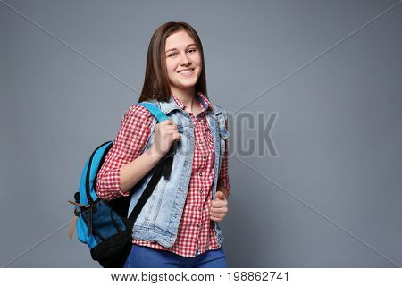 Young smiling girl with knapsack on grey background