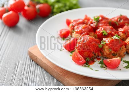 Plate with delicious turkey meatballs and tomato sauce on table, closeup