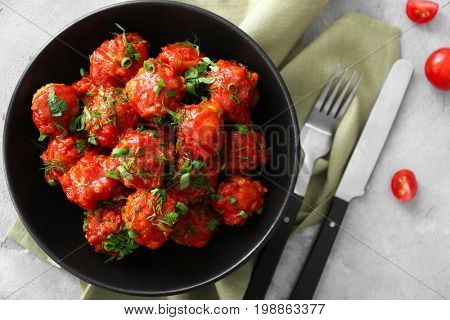 Plate with delicious turkey meatballs and tomato sauce on table